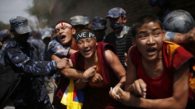 Un grupo de tibetanos son detenidos por la fuerza por la policía nepalí durante una protesta pro-tibetana fuera del consulado chino el 30 de marzo de 2008 en Katmandú, Nepal.