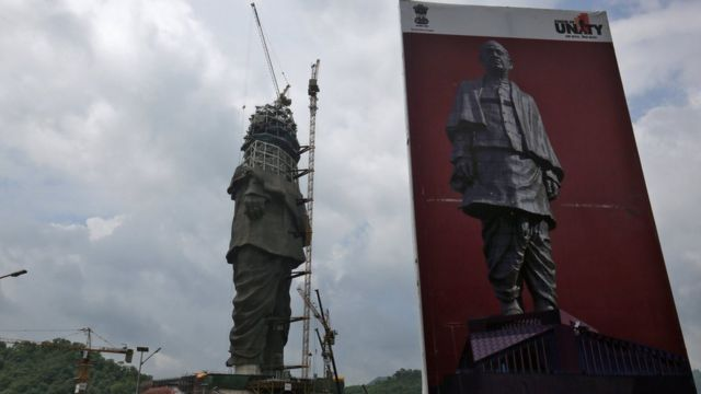 Imagen de la estatua junto a un póster de la obra final.
