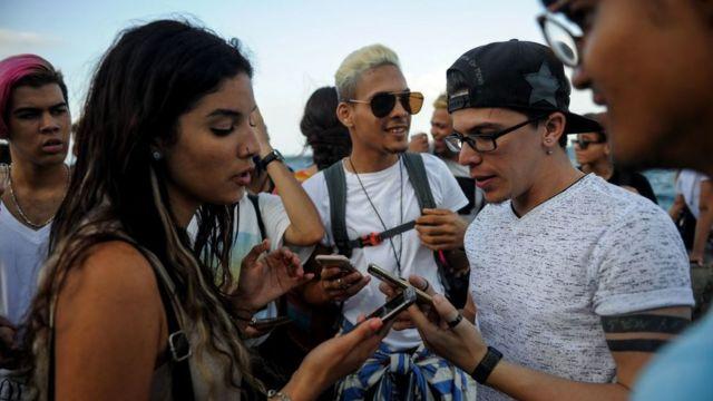 Jovens olham seus telefones no Malecón, em Havana