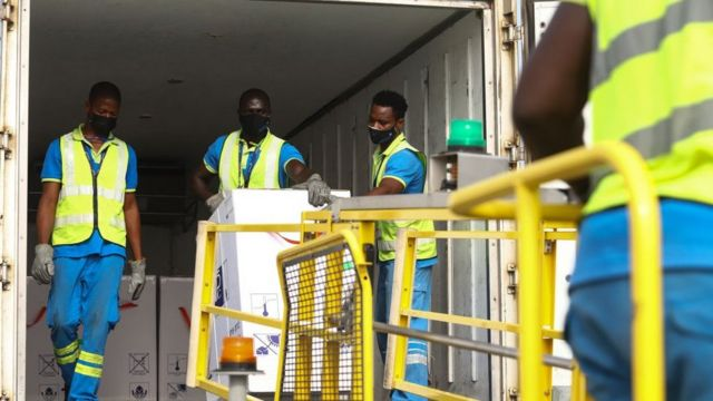 Men in hi-vis jackets dealing with a vaccine delivery
