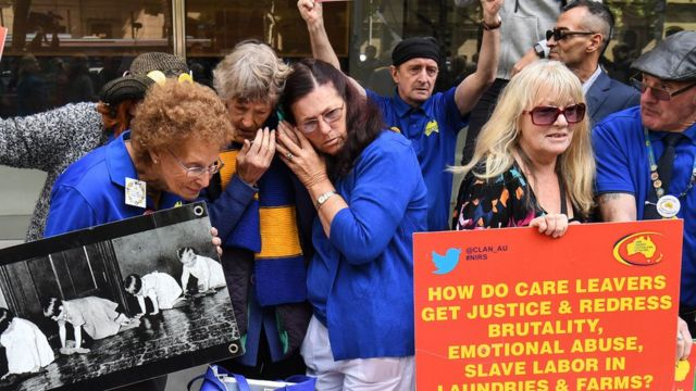 People huddle over a phone to listen to the judge's sentencing remarks while other protesters hold signs outside the court