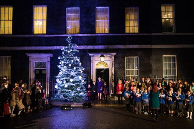 英國首相特里莎·梅和她的選區三名女學生為唐寧街10號門外的聖誕樹亮燈。