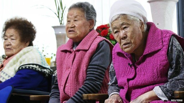 """Former South Korean """"comfort women"""" watch a news report as they wait for the result of meeting between foreign ministers of South Korea and Japan"""