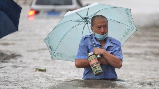 A man wading through flood waters along a street following heavy rains in Zhengzhou