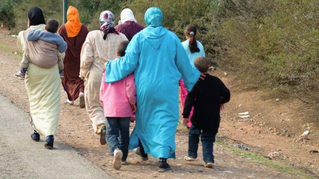 Mujeres y niños caminando
