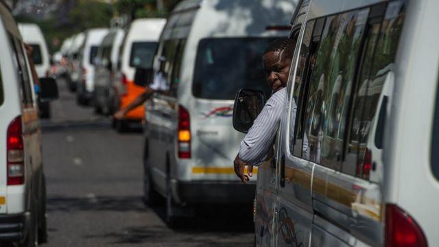 Niz minibus taksija na putu, dok jedan vozač gleda kroz prozor
