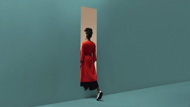 Mulher em um vestido vermelho passando por um buraco em uma parede azul