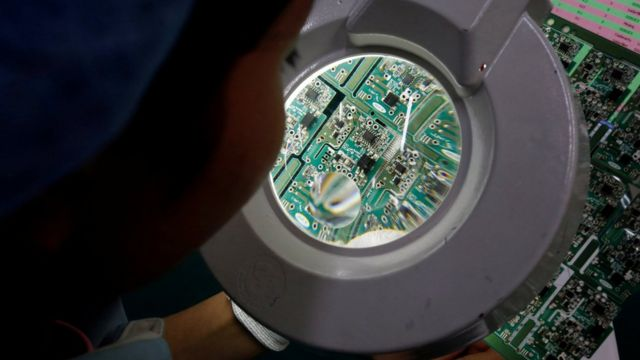 A woman looks through a magnifying glass to check errors of a printer circuit board at Manutronics Factory in Bac Ninh province, Vietnam May 30, 2018.