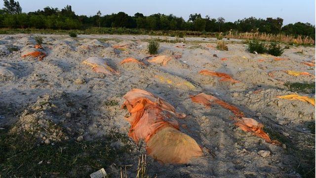 Valas feitas informalmente para vítimas da covid nas areias das margens do Ganges