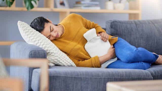 Mujer tumbada en un sofá con dolor abdominal.