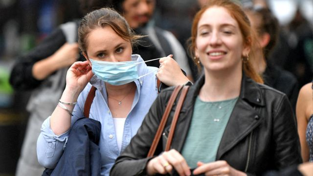 A shopper puts on a protective face covering in London