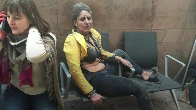 Woman covered in dust looking at camera after explosion in Brussels airport - March 2016