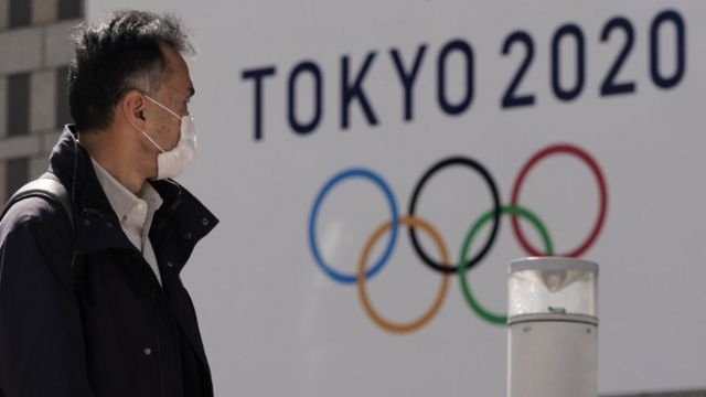 A pedestrian wearing a mask walks past the emblem of Tokyo 2020 Olympics in Tokyo.