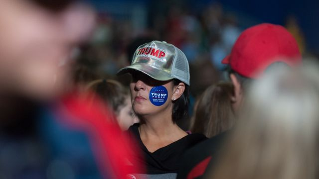 Woman wearing trump sticker on her cheek at rally