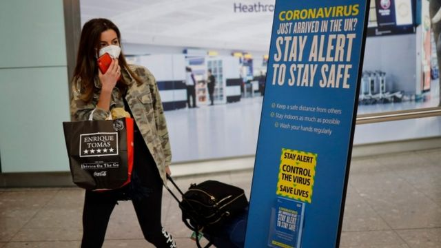 Woman wearing a face mask arrives at Heathrow airport