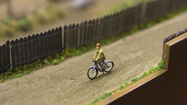 Велосипедист, який їде дорогою неподалік колій