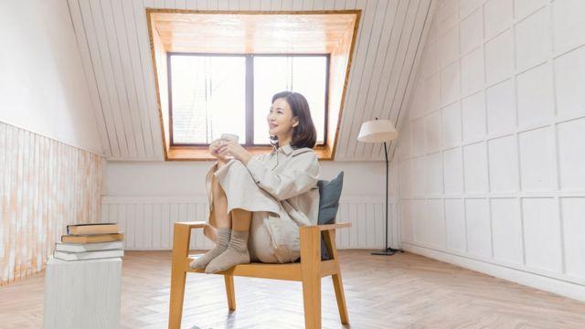 Mulher sorrindo em poltrona dentro de casa