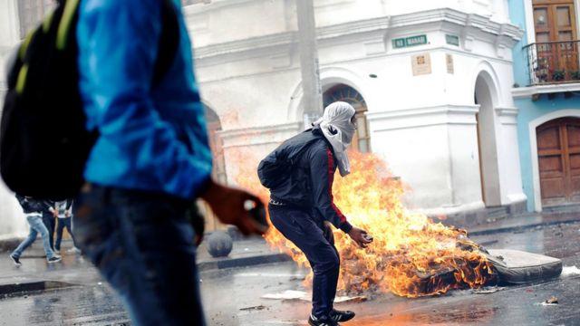 Dos personas protestan en Ecuador y de fondo se ve un colchón en llamas