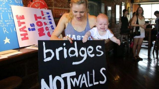 """مراسلة في بانكوك تحمل لافتة كتب عليها """"جسور وليس جدران"""""""