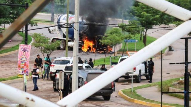 Hombres armados junto a un vehículo incendiado