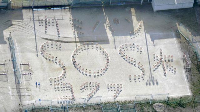 熊本国府高校の校庭には椅子で作った「カミ パン SOS 水」のメッセージが並んだ