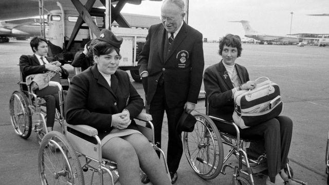 A equipe britânica deixando o Aeroporto Heathrow de Londres para os Jogos Internacionais de Stoke Mandeville em Israel, em 1968. Ludwig Guttmann, presidente e fundador dos jogos, é retratado com Karen Hill, de Mansfield, de 18 anos