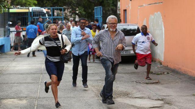 Pessoas correm após abertura dos portões em local de votação na Rocinha, no Rio