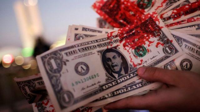Mão segura notas de dólar falsas com foto de Bolsonaro e marcas de sangue