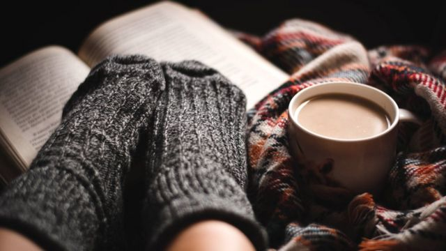 Libro, taza de café y pies con medias