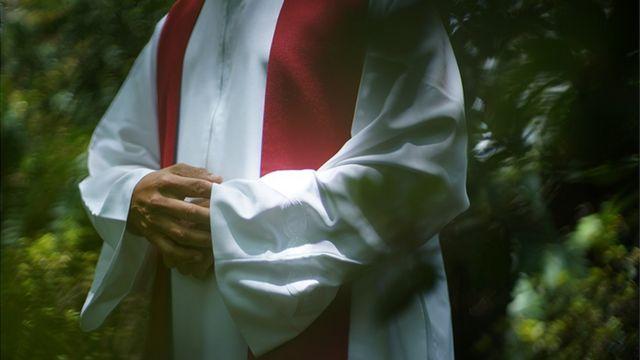 Un sacerdote con alba blanca y una estola bermellón sobre los hombros