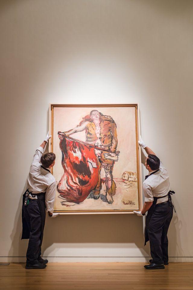 Двое мужчин вешают картину