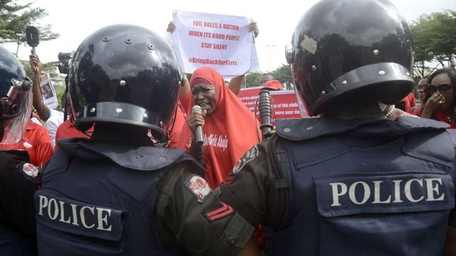 Riot police officers dey in front of pipo wey dey protest say make goment epp resuce pikin wey Boko Haram don kidnap