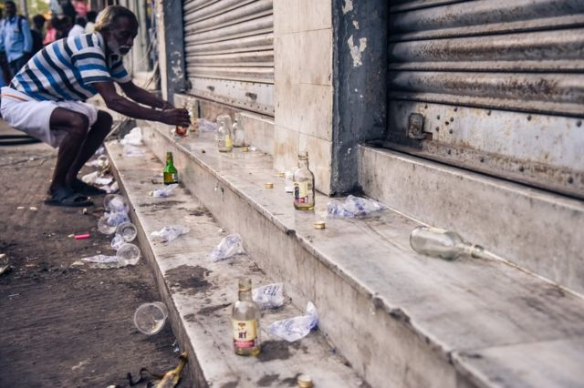Empty bottles and cups are strewn about near alcohol shops