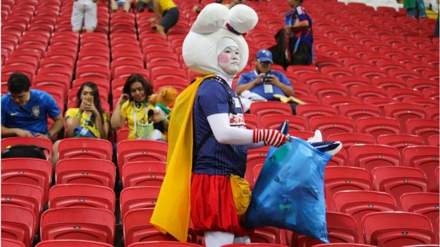 Japan football fan with a bag full of rubbish