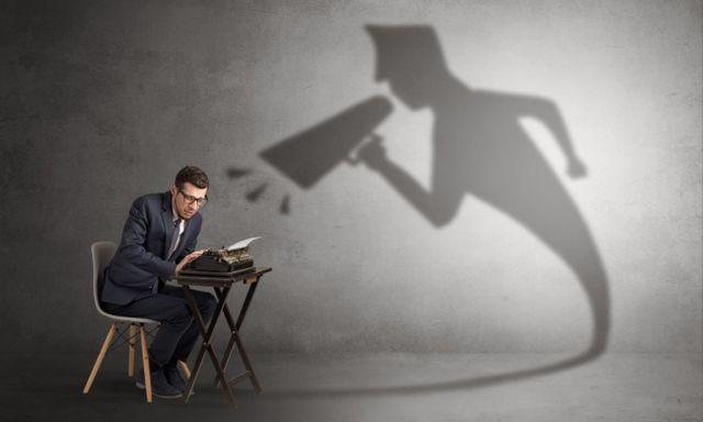 Un homme avec une machine à écrire et l'ombre de quelqu'un qui crie.