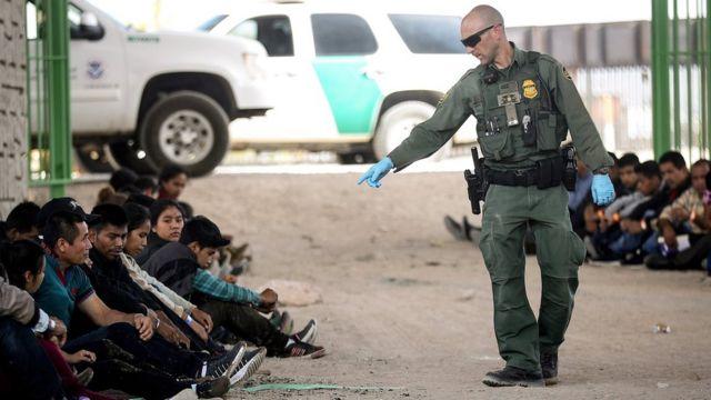 Un agente de la Patrulla Fronteriza señala a un grupo de migrantes detenidos en la frontera entre EE.UU. y México.