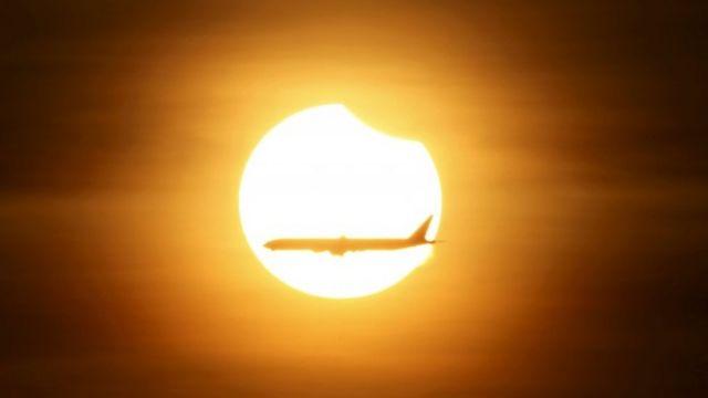 シンガポール上空で部分日食の前を通過する飛行機(9日)