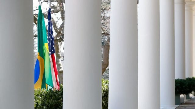 Bandeiras do Brasil e dos EUA entre colunas da Casa Branca