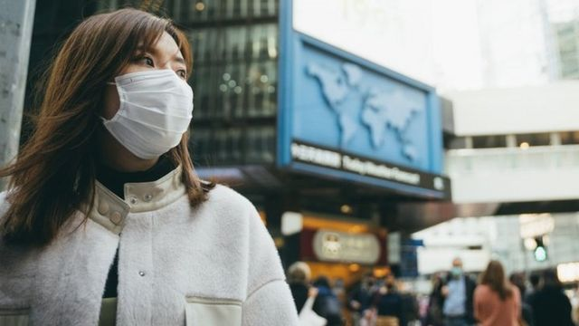 A woman wearing a mask in a city