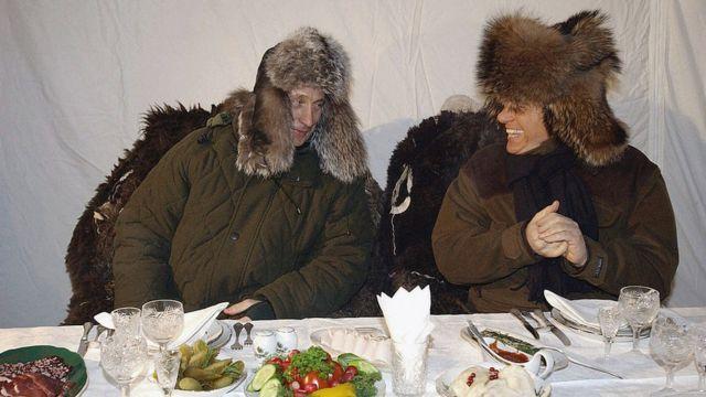 Putin na Berlusconi wakiwa wamevalia nguo za msimu wa baridi katika eneo la uhifadhi wa wanyama pori kaskazini mwa Moscow 2003