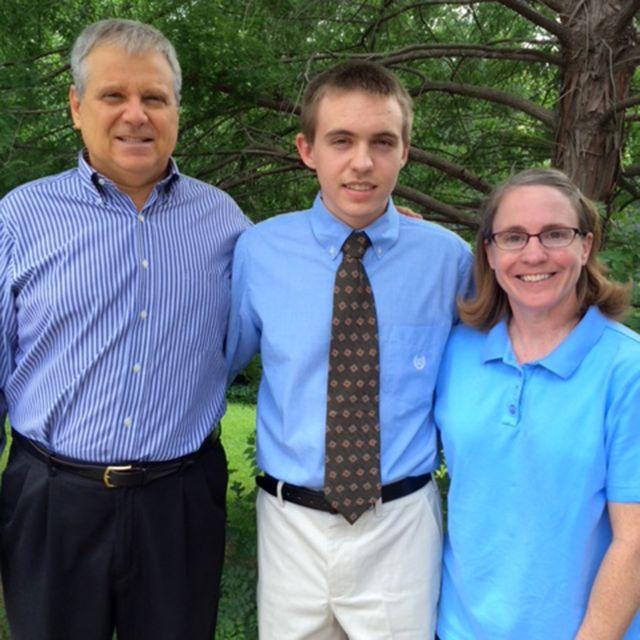 Jim posa para foto ao lado da esposa e do filho no dia da formatura dele