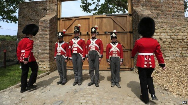 Actors play the part of soldiers outside the gate of Hougmount Farm in Belgium where the battle of Waterloo was fought.