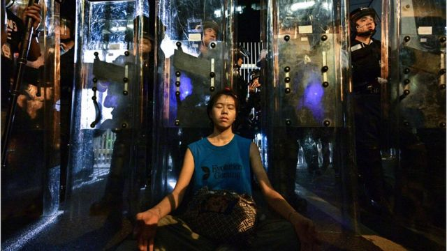 A woman (C) meditates in front of a line of riot police standing guard with their shields outside the government headquarters in Hong Kong early on June 12, 2019