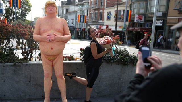 Umupfasoni ariko arifotoza iruhande y'igishusho ca Donald Trumpmu gisagara ca San Francisco
