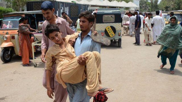 A Pakistani relative carries a heatstroke victim to a hospital in Karachi