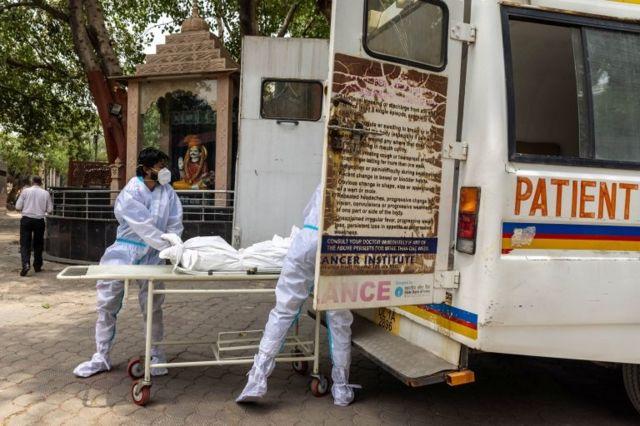 कोभिडका कारण नयाँ दिल्लीमा मृत्यु भएका एक व्यक्तिको शव निकालिँदै