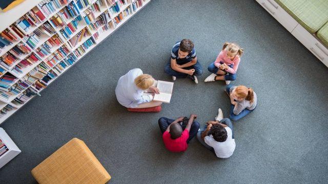 Uma professora lê para um grupo de crianças no chão de uma biblioteca