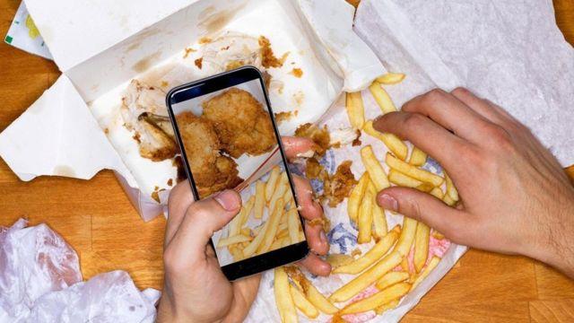 Una persona tomando una foto con su celular de una comida con pollo y papas fritas