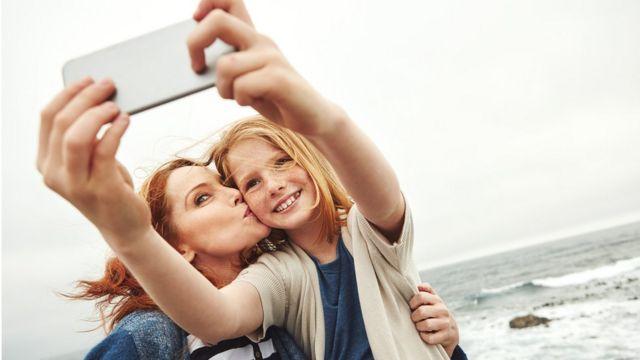 niña y madre usando celular