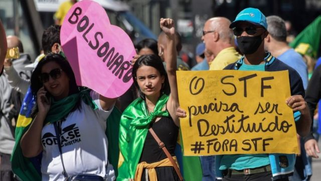 Três manifestantes em rua segurando cartaz em formato de coração dizendo 'Bolsonaro' e outro 'O STF precisa ser destituído'